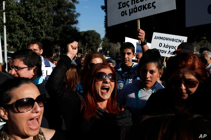 Protesters shout slogans outside parliament in Nicosia, Cyprus, March 18, 2013.