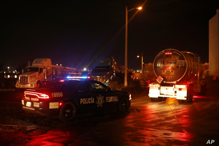 Federal police escort loaded fuel tankers carrying gasoline to parts of the country suffering shortages as they leave a Petroleos Mexicanos, or Pemex, fuel depot and distribution center in the port city of Veracruz, Mexico, Jan. 9, 2019.