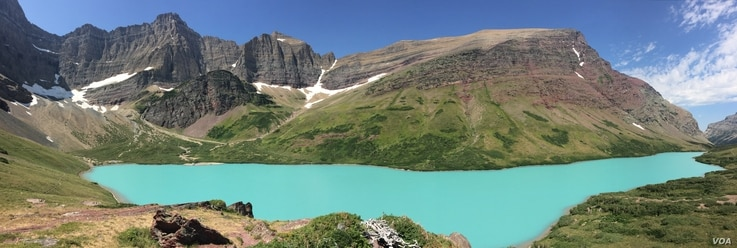 With its stunning turquoise waters, Cracker Lake stands out like a jewel against a backdrop of greens and grays.