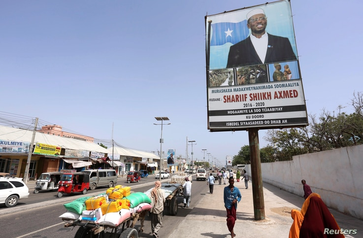 People walk along a street with the campaign billboard of Somalia's Presidential candidate Sharif Sheikh Ahmed in Somalia's capital Mogadishu, Feb. 6, 2017.