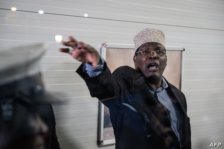 Kenyan opposition politician Miguna Miguna, who also holds Canadian citizenship and travels on a Canadian passport, reacts after Kenyan immigration authorities denied him entry into the country without a Kenyan visa, at Jomo Kenyatta International Ai...