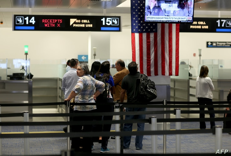 FILE - International travelers wait in line at a U.S. Customs and Border Protection checkpoint after arriving at Miami International Airport on March 4, 2015, in Miami, Florida.