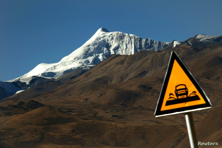 A road sign is seen in front of the Kharola glacier