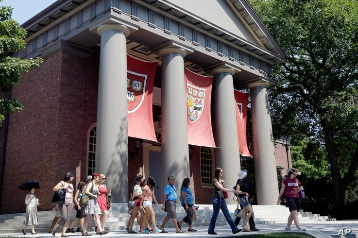 File - A tour group walks through the campus of Harvard University in Cambridge, Massachusetts.