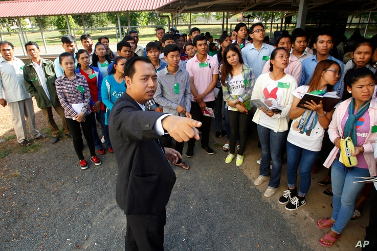 Cambodian court officer Neth Pheaktra guides students outside the court hall before the first appeal hearings against two former Khmer Rouge senior leaders, Khieu Samphan and Nuon Chea, at the U.N.-backed war crimes tribunal in Phnom Penh, Cambodia, ...