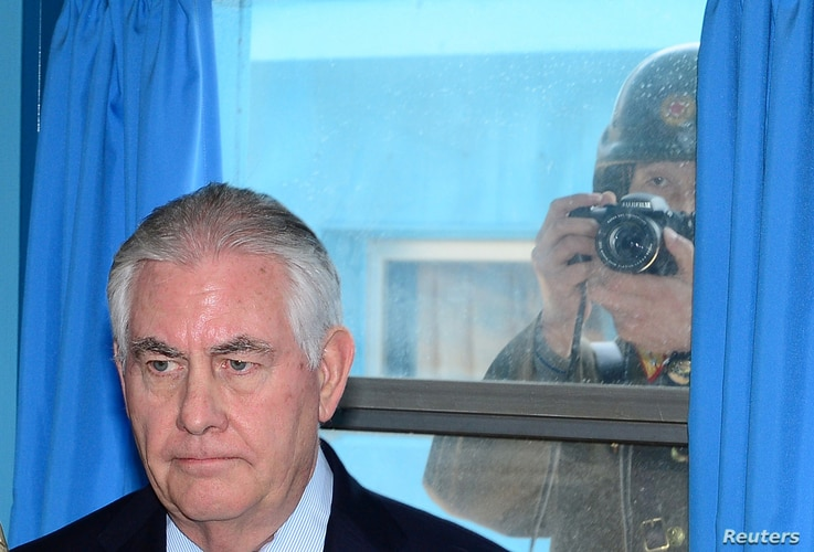 U.S. Secretary of State Rex Tillerson is briefed by U.S. Gen. Vincent K. Brooks, commander of the United Nations Command, Combined Forces Command and United States Forces Korea (not pictured), as a North Korean soldier takes a photograph through a wi...