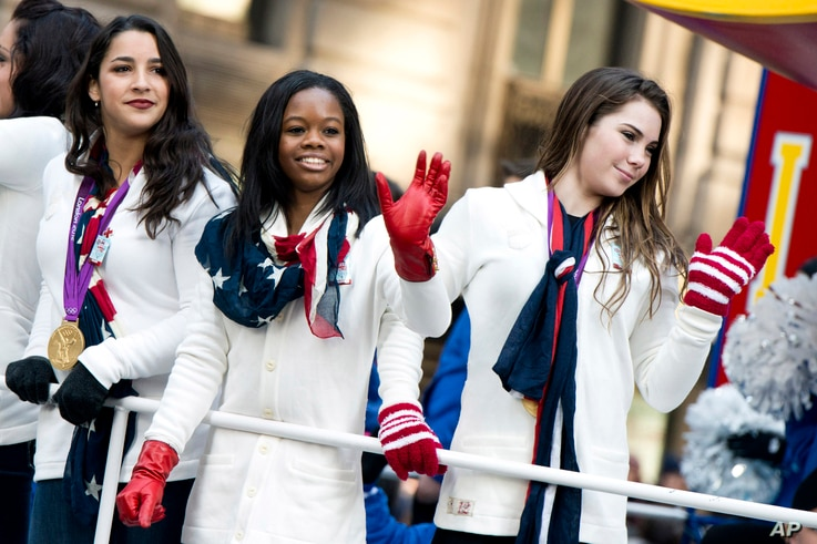 FILE - U.S. gymastics team members, from right, McKayla Maroney, Gabby Douglas and Aly Raisman ride a float in the Macy's Thanksgiving Day Parade in New York, Nov. 22, 2012. All three are among the women who have publicly said they were among Dr. Lar...