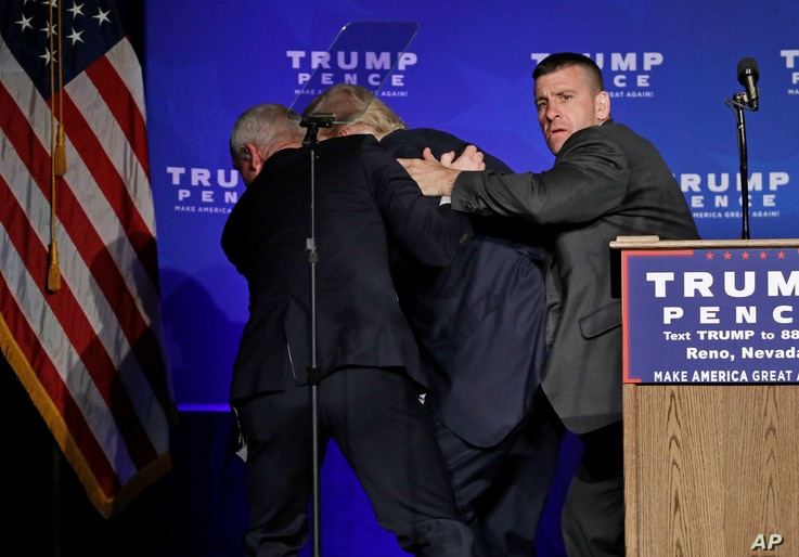 Secret Service agents rush Republican presidential candidate Donald Trump off the stage at a campaign rally in Reno, Nev., Nov. 5, 2016.