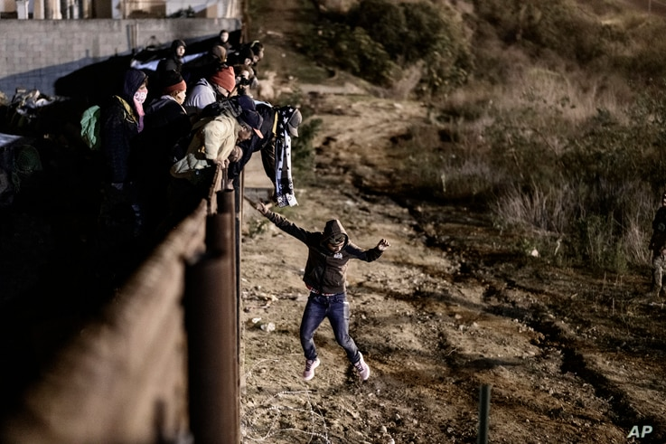 A migrant jumps the border fence to get into the U.S. side to San Diego, Calif., from Tijuana, Mexico, Jan. 1, 2019.