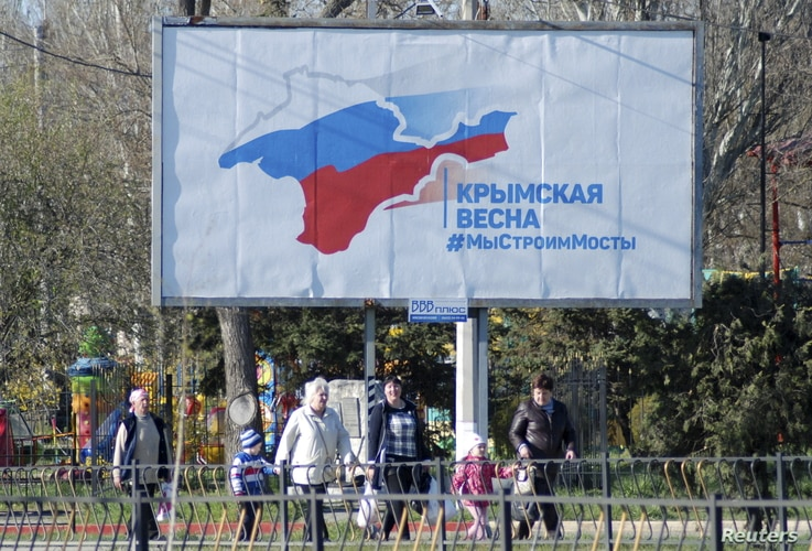 """A billboard, which promotes the construction of a bridge across the Kerch Strait to the Krasnodar region, is displayed on a street in Kerch, Crimea, April 5, 2016. The board reads: """"Crimean spring. We build bridges."""""""
