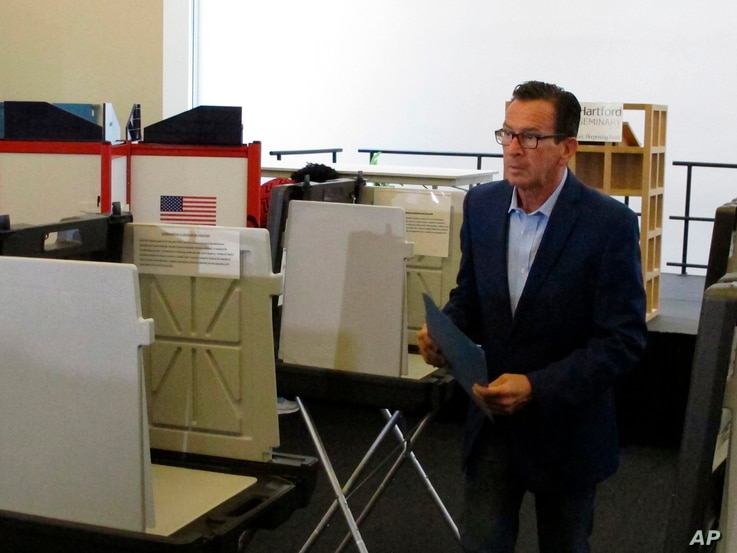 Gov. Dannel P. Malloy prepares to submit his ballot for the primary election at a polling place in Hartford, Connecticut, Aug. 14, 2018.