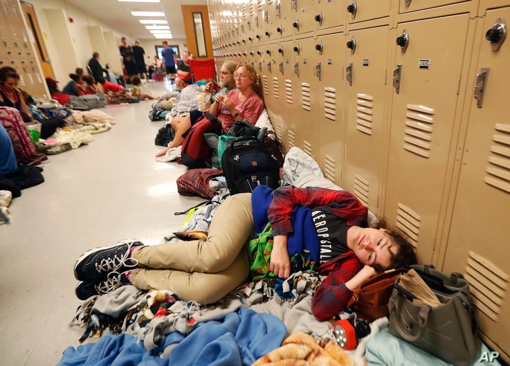 Emily Hindle lies on the floor at an evacuation shelter set up at Rutherford High School, in advance of Hurricane Michael, which made landfall, in Panama City Beach, Fla., Oct. 10, 2018.