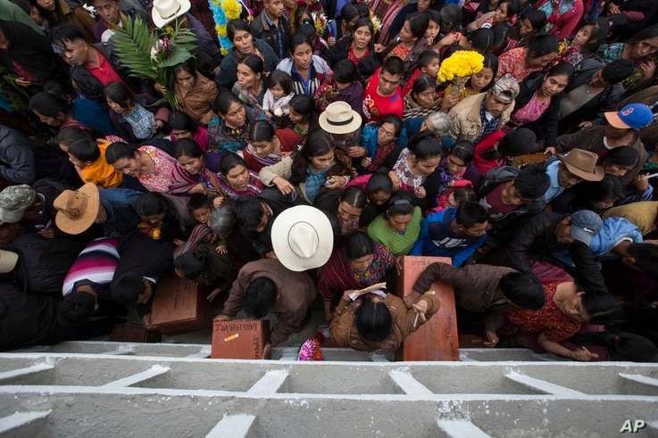 FILE - Villagers place the remains of their recently identified relatives killed during the civil war, in niche graves at the cemetery of Santa Avelina, Guatemala, Nov. 30, 2017.