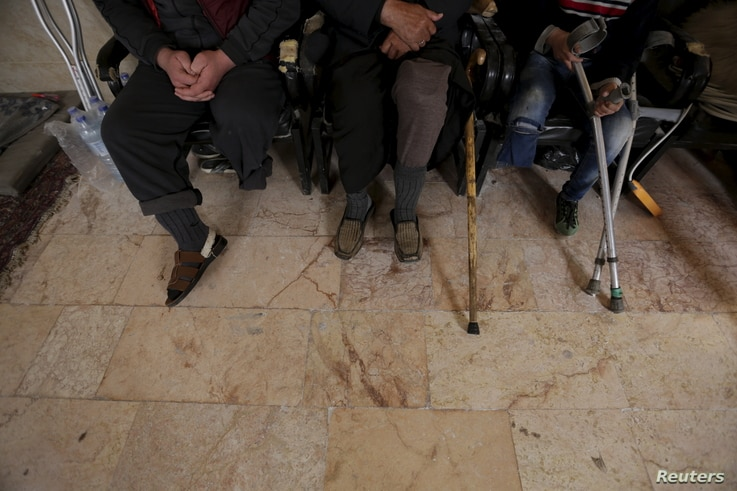 Men with amputated limbs wait to be inspected in the rebel-controlled area of Maaret al-Numan town in Idlib province, Syria, March 20, 2016.