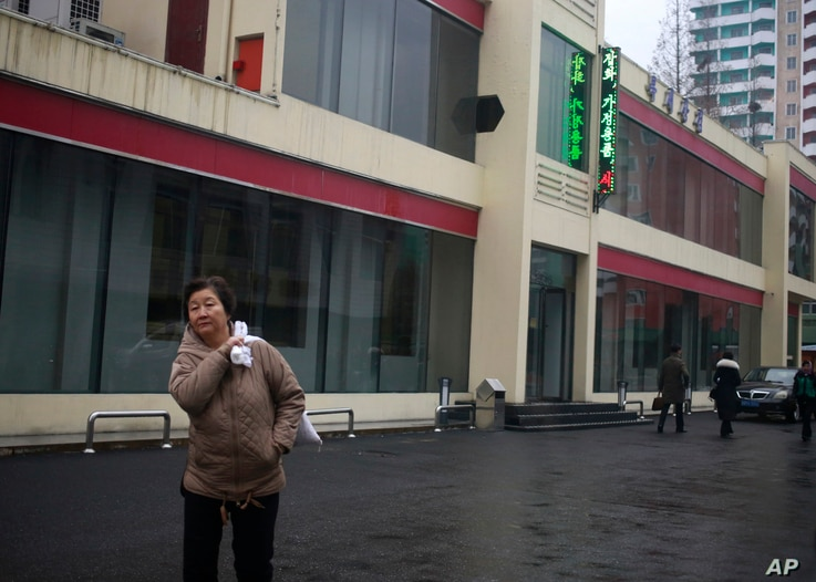 """FILE - In this Dec. 21, 2018, photo, a North Korean woman walks outside Bugsae Shop, also known as the """"Singapore Shop,"""" in Pyongyang. Business is booming at such shops, which sell everything from Ukrainian vodka to brand-name knock-offs from China. ..."""
