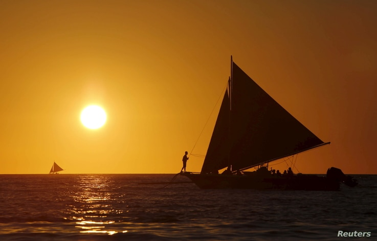 Tourists catch a glimpse of the sunset while sailing along the island of Boracay, central Philippines January 17, 2016.