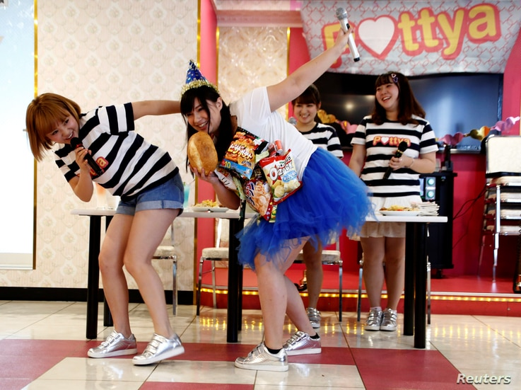 Michiko Ohashi (C), wearing a costume decorated with snacks, performs with other members of pop group Pottya at a fan meeting celebrating her birthday in Tokyo, Japan, Oct. 16, 2016.