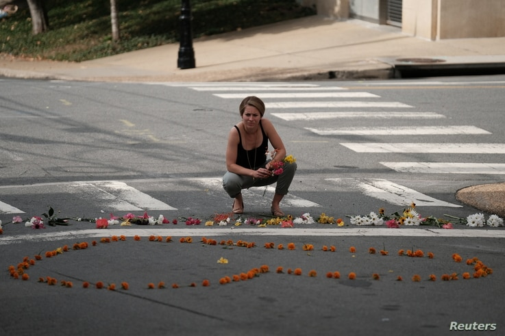 """A woman kneels at a makeshift memorial for the victims of a car that plowed into counter-protesters after a """"Unite the Right"""" rally organized by white nationalists in Charlottesville, Virginia, Aug. 13, 2017."""