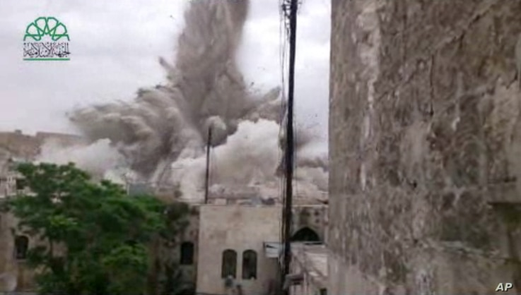 This image made from amateur video posted by Shaam News Network (SNN), an anti-Bashar Assad activist group, shows an explosion that destroyed the Carlton Hotel in Aleppo, Syria, May 8, 2014.