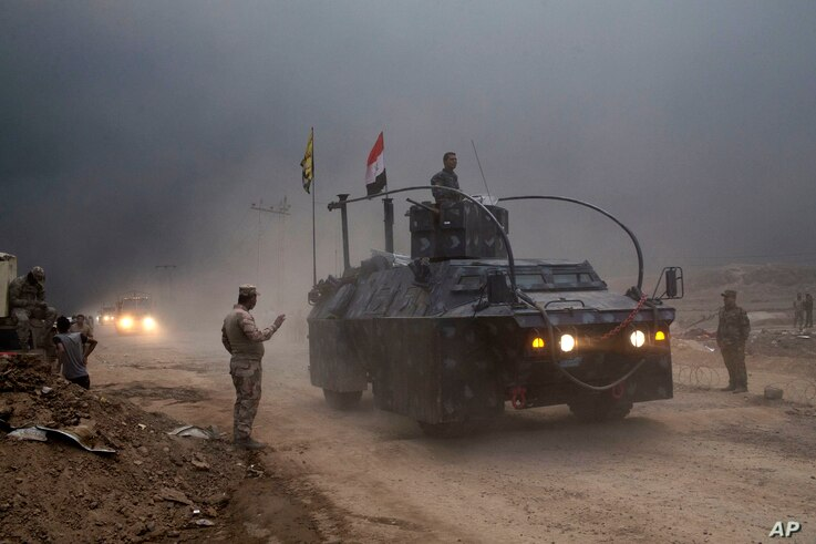 An Iraqi Federal Police vehicle passes through a checkpoint in Qayyara, 50 kilometers south of Mosul, Iraq, Oct. 26, 2016. Islamic State militants have been going door to door in farming communities south of Mosul, ordering people at gunpoint to foll...