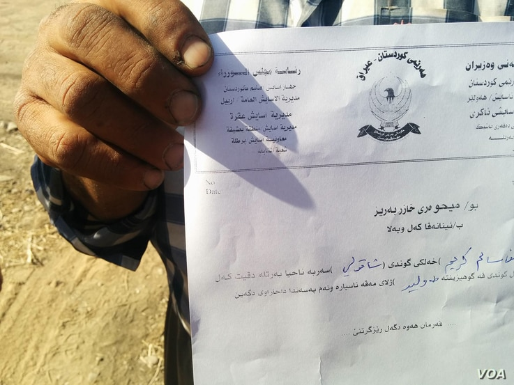 One man holds up a paper issued to him by peshmerga forces, allowing him to enter into the area, still generally off limits to civilians, in Kazir province of Kurdistan in Iraq, Oct. 22, 2016. (H. Murdock/VOA)