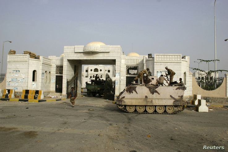 Army soldiers guard the gate of the local authority's compound in the southern Yemeni city of Zinjibar after the army retook the city from al-Qaida-linked militants, June 12, 2012.