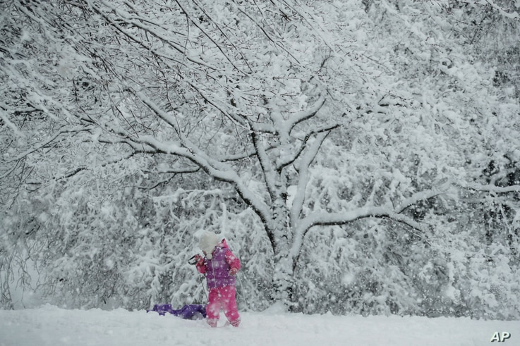 A young girl plays in the snow during a winter storm, March 7, 2018, in Marple Township, Pennsylvania.