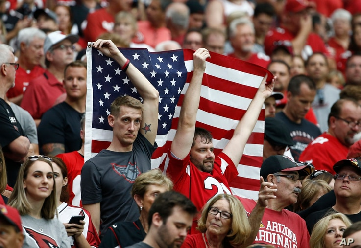Arizona Cardinals and San Francisco 49ers fans hold the American flag during the national anthem prior to an NFL football game, Oct. 1, 2017, in Glendale, Arizona.