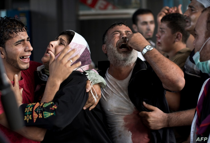 Palestinian mourners cry at Gaza City's al-Shifa hospital after an explosion killed at least seven children in a public playground in the beachfront Shati refugee camp on July 28, 2014.