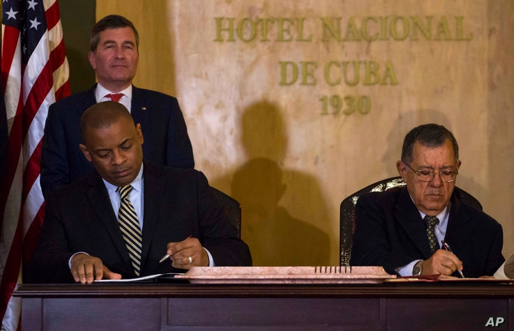 U.S.Transportation Secretary Anthony Foxx and Cuba's Minister of Transportation Adel Yzquierdo Rodriguez, right, sign the airline transportation agreement as Assistant Secretary of State for Economic and Business Affairs Charles Rivkin, top left, loo...