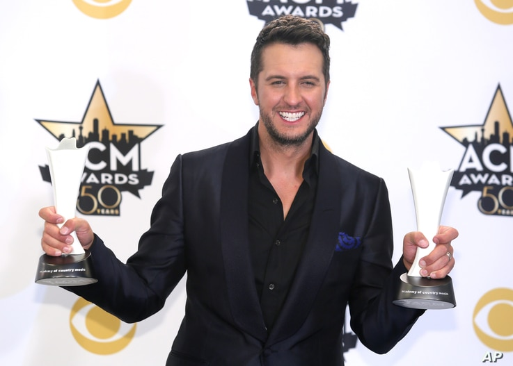 Luke Bryan poses in the press room with the awards for entertainer of the year and vocal event of the year at the 50th annual Academy of Country Music Awards at AT&T Stadium, April 19, 2015, in Arlington, Texas.