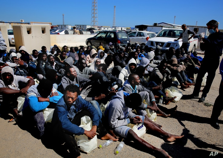 African illegal migrants wait to receive medial assistance after being rescued by coastal guards on a port in Tripoli, Libya, Monday, April 11, 2016.