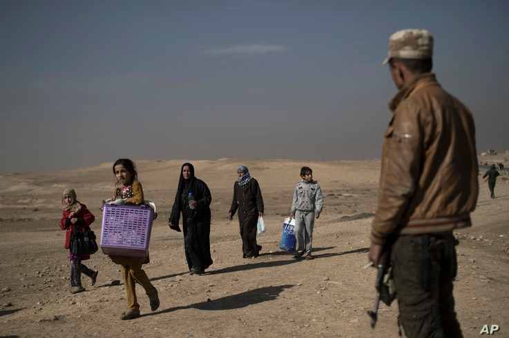 FILE - Displaced people leave their homes during fighting in Hamam al-Alil, south of Mosul, Iraq, Nov. 6, 2016.