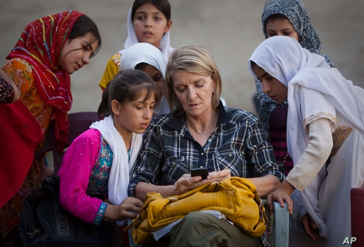 In this Saturday, Oct 1, 2011 photo, AP Special Regional Correspondent for Afghanistan and Pakistan Kathy Gannon sits with girls at a school in Kandahar, Afghanistan.