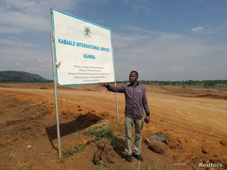 Christop Opiyo point at where his house used to be in Kabaale village before they were evicted for the construction of an airport in Hoima District, Uganda, July 14, 2018.