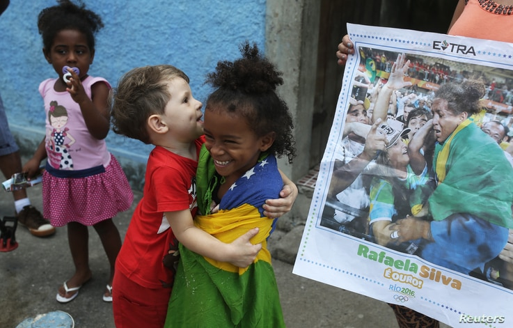 File -- Cousins of Brazilian judoka Rafaela Silva who won the gold medal in the 57 kg judo final, joke beside a newspaper with the picture of her next to the house where she was born at the City of God slum.