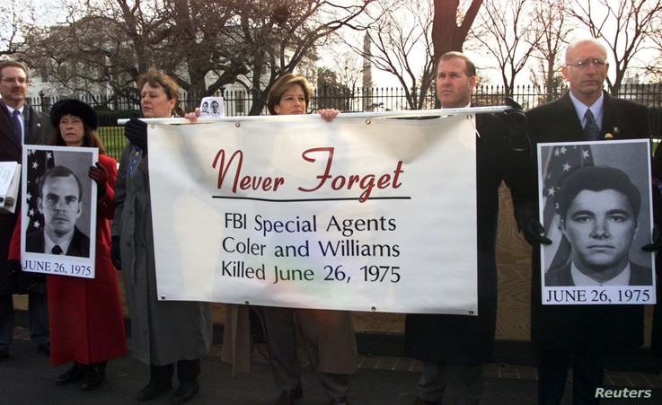 FBI Agents hold a banner in front of the White House during an FBI rally, December 15, 2000. The rally was held to show opposition to any consideration by then-President Bill Clinton to grant clemency to Leonard Peltier, convicted of murdering two FB...