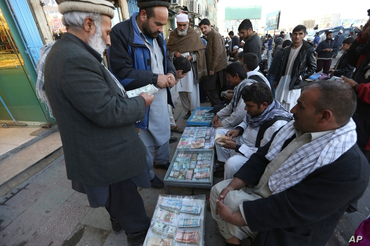An Afghan money changer, second from right, counts a pile of Pakistani currency banknotes at a money exchange market in Kabul, Dec. 5, 2016.