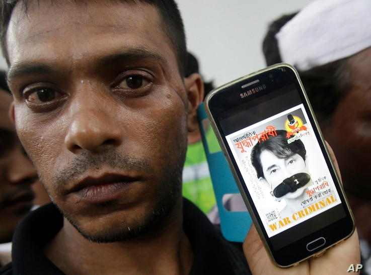 A Rohingya protester shows his mobile phone displaying a portrait of Myanmar's Foreign Minister Aung San Suu Kyi with her mouth covered with a sandal during a demonstration in front of the Myanmar Embassy in Bangkok, Thailand, Nov. 25, 2016 against ...