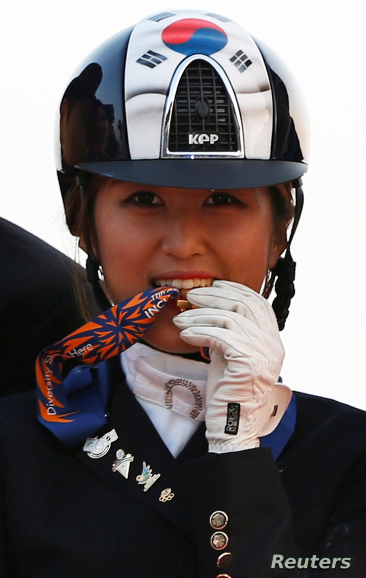 FILE - South Korea's Chung Yoo-ra, then known as Chung Yoo-yeon, bites her gold medal as she poses after winning the equestrian Dressage Team competition at the Dream Park Equestrian Venue during the 17th Asian Games in Incheon, Sept. 20, 2014.