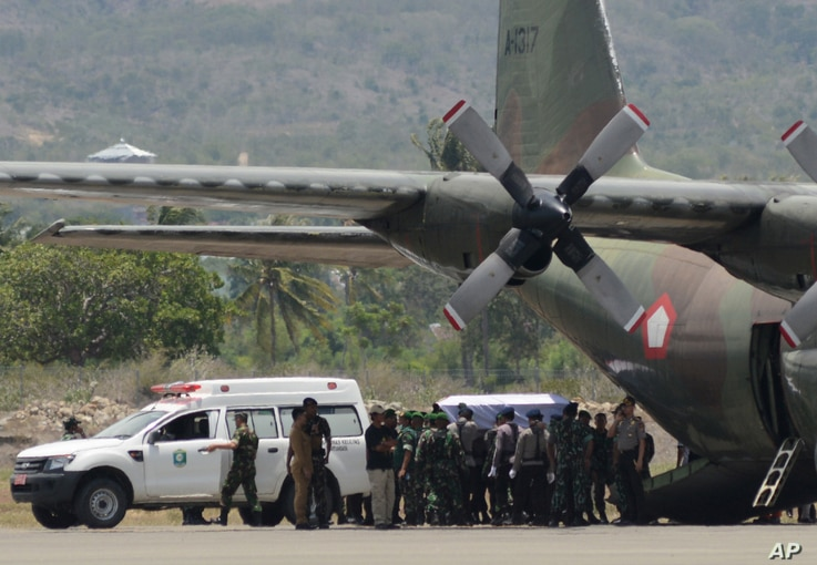 A coffin containing the body of one of the victims of a military helicopter crash in Poso, Central Sulawesi, is loaded into a cargo plane to be transported to Jakarta at the airport in the provincial capital of Palu, Indonesia, March 21, 2016.