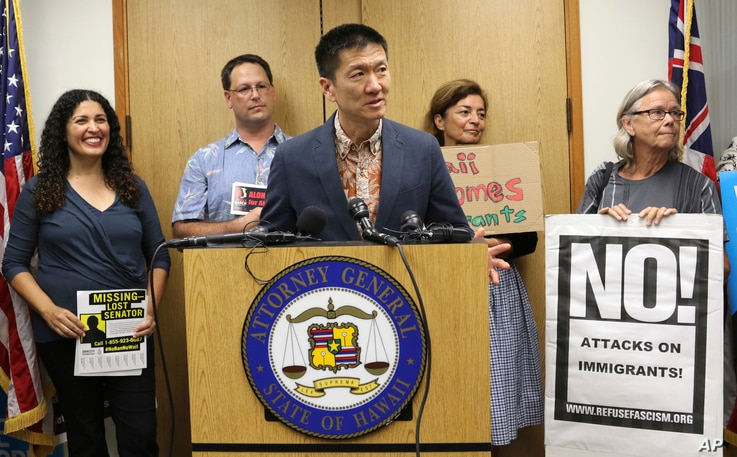 FILE - Hawaii Attorney General Douglas Chin speaks about President Donald Donald Trump's travel ban in Honolulu. A federal judge in Hawaii on Thursday left Trump administration rules in place for a travel ban on citizens from six majority-Muslim coun...
