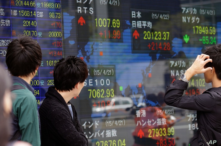 People look at an electronic stock indicator of a securities firm in Tokyo. Asian stocks were mostly higher Wednesday after Japan reported its first trade surplus in three years, April 22, 2015.