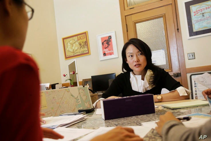 FILE - City supervisor Jane Kim talks to members of her staff as she is interviewed at City Hall in San Francisco, June 26, 2017.