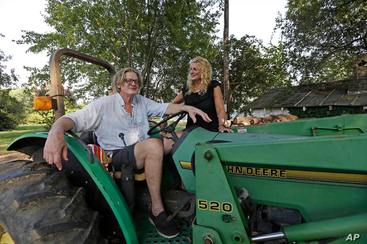 Tom and Heather LaGarde are seen on Tom's tractor at their home near Saxapahaw, N.C., on Aug. 29, 2018. The LaGardes left New York following the events of 9/11.