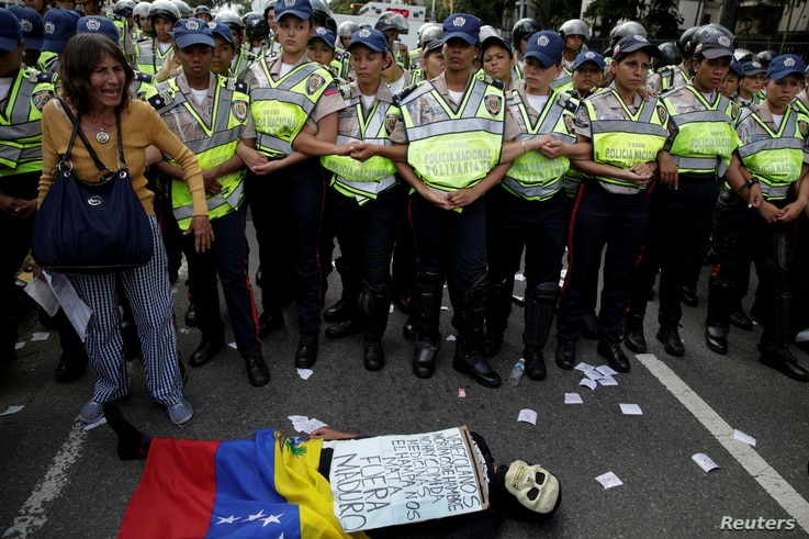 """An opposition supporter wearing a costume lies in front of riot police during a rally against Venezuelan President Nicolas Maduro's government in Caracas, Venezuela Jan. 23, 2017. The sign reads """"Venezuelans starve. There is no food or medicine. The ..."""