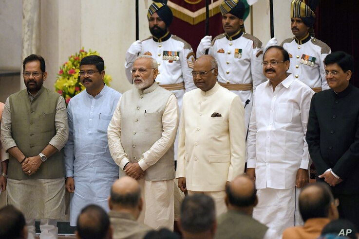 India Prime Minister Narendra Modi, third left, President Ramnath Kovind, third right and Vice President Venkiah Naidu, second right, pose with the newly sworn-in ministers Mukhtar Abbas Naqvi, left, Dharmendra Pradhan, second left and Piyush Goyal, ...