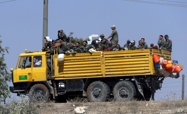Syrian army soldiers sit aboard a truck near the village of Sh.Miskin, Syria, Aug. 14, 2018.