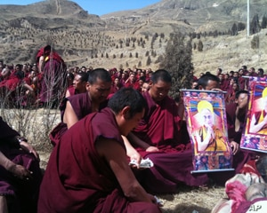 Monks praying in front of body at a cremation site