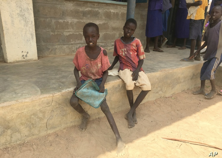 In this photo taken April 6, 2017, nine-year-old, Thor Athiam , left, and his classmate eagerly wait with their lunchboxes for World Vision's daily hot meal in Rumathoil, South Sudan.